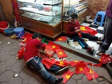 Những đứa trẻ không giấu nổi niềm vui khi cùng nhau xếp cờ đỏ sao vàng chúc mừng đội tuyển Việt Nam.