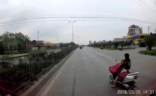 Tin nhanh - Thót tim: Mẹ vừa đèo con vừa cởi áo mưa, suýt gây họa trên quốc lộ